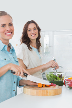 Women preparing a salad together smiling at camera in the kitchen  photo