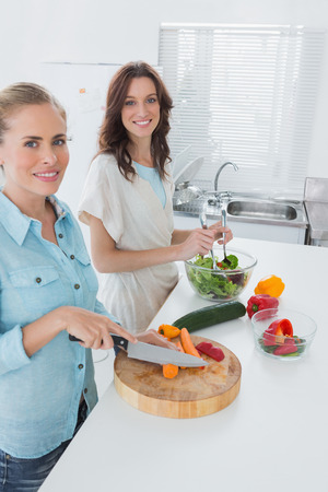 Women cooking together in the kitchen and looking at camera photo