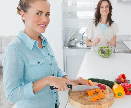 Blonde woman cutting carrots with her friend tossing salad in the kitchen photo