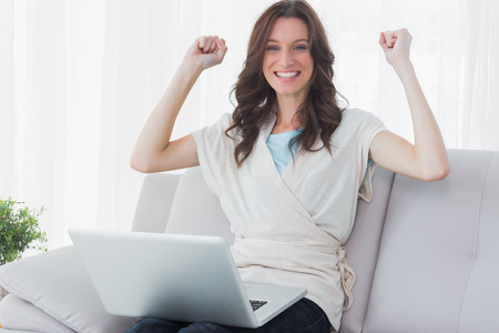 Cheering woman with laptop on her knees and sitting on the couch photo