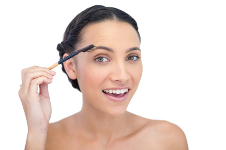 Surprised young brunette using eyebrow brush on white background Stock Photo - 25739477