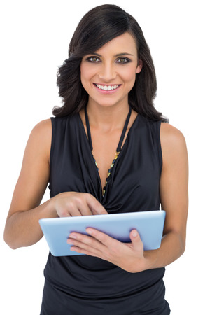scrolling: Smiling elegant brown haired model scrolling on tablet pc on white background