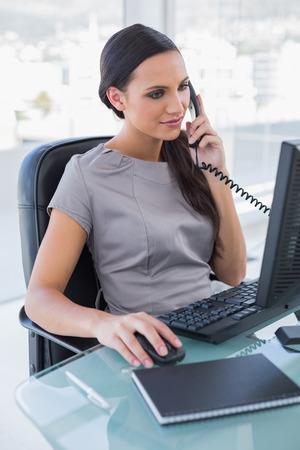 answering phone: Empresaria concentrada contestar tel�fono y de trabajo en equipo en su oficina Foto de archivo