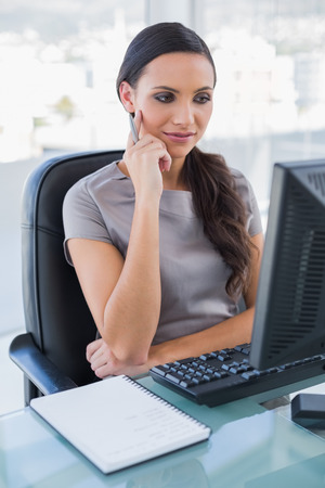 classy woman: Thoughtful gorgeous businesswoman looking at her computer screen in her office