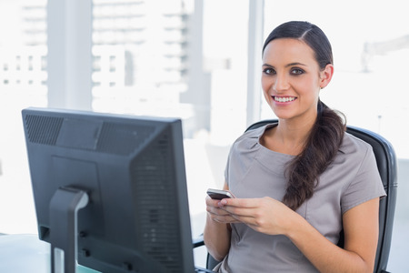 Happy dark haired businesswoman holding phone in her office photo