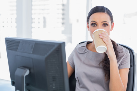 Attractive businesswoman in her office drinking coffee and looking at camera photo