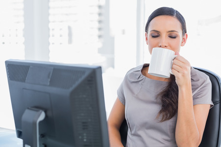 Smiling attractive businesswoman drinking tea in her office photo