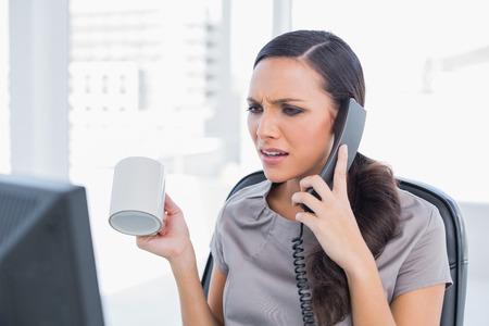 answering phone: Secretario Irritado contestar el tel�fono en su oficina y mirando la pantalla del ordenador