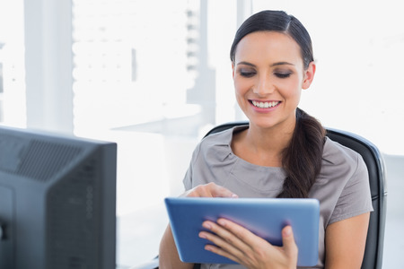scrolling: Cheerful attractive secretary scrolling on tablet pc in her office