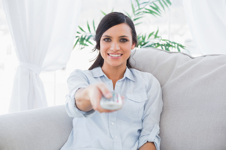 changing channel: Happy gorgeous brunette changing tv channels in living room Stock Photo