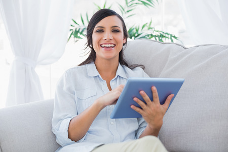 Smiling brunette with tablet pc in living room photo