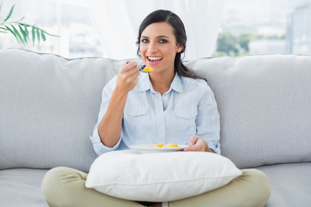 crossing legs: Cheerful woman sitting on the couch crossing legs eating fruits in her living room