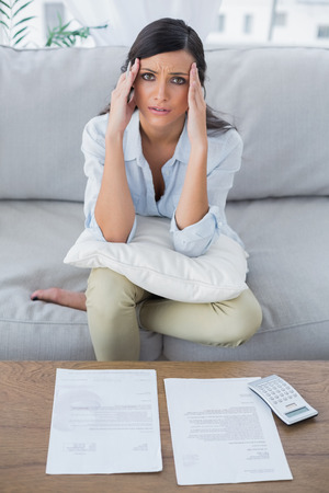 Fed up woman checking her bills in her living room photo