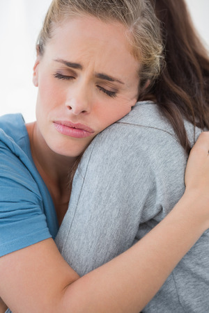 closing eyes: Woman taking her sad friend in her arms while closing eyes