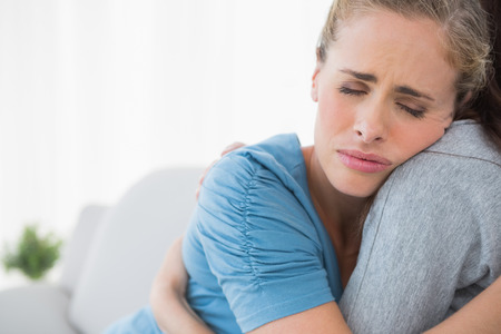 Upset woman being consoled by her friend and closing eyes Stock Photo
