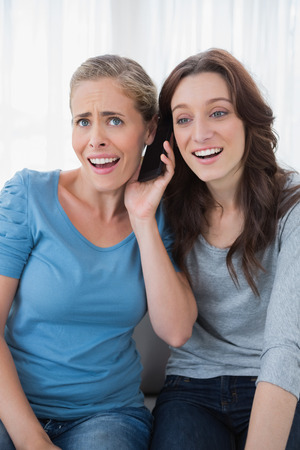 intriguing: Surprised friends listening to something intriguing on the phone and sitting on the sofa