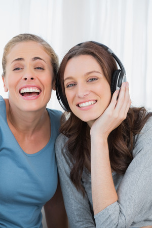 Laughing women listening to music sitting on the sofa