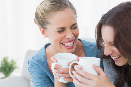 tied woman: Friends bursting out laughing while having coffee sitting on the sofa