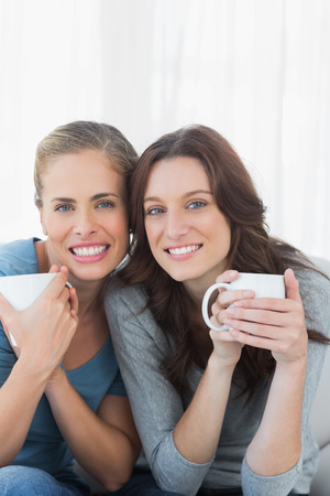 women friends: Cheerful women holding their cup of coffee sitting on the sofa