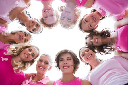 白い背景の乳癌のピンクを着て輪に幸せな女性のグループ
