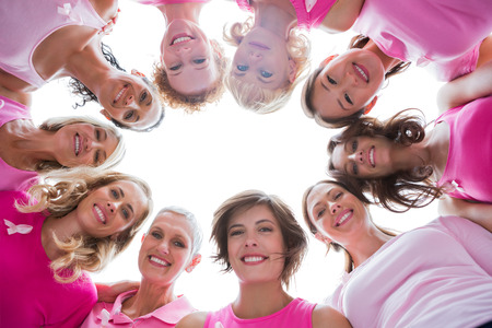 Group of happy women in circle wearing pink for breast cancer on white background