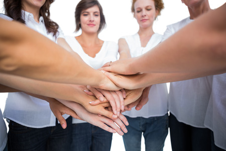 Relaxed women joining hands in a circle on white background