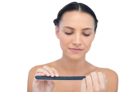 Peaceful natural young model using nail file on white background Stock Photo - 25742186