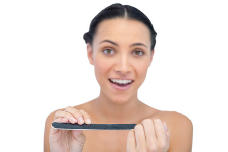 Surprised young model with nail file on white background Stock Photo - 25742185