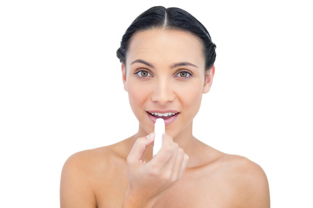 chap: Happy natural model applying chap stick on white background Stock Photo