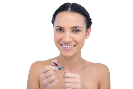 nail clippers: Cheerful natural model using nail clippers on white background