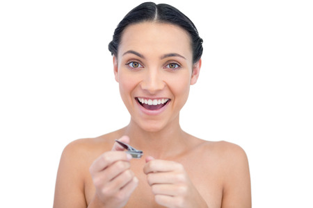 Enthusiastic natural model using nail clippers on white background Stock Photo - 26733342
