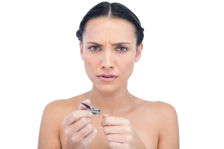 Frowning young model using nail clippers on white background Stock Photo - 25740596