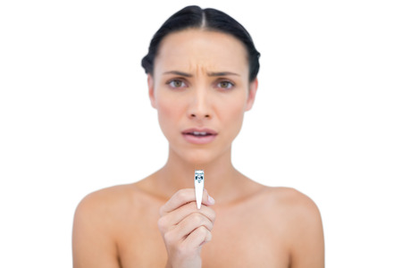 nail clippers: Frowning young brunette holding nail clippers on white background
