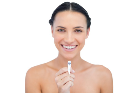 Cheerful brunette posing with nail clippers on white background Stock Photo - 25740608