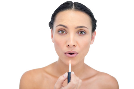 Young model applying lip gloss while looking at camera on white background photo