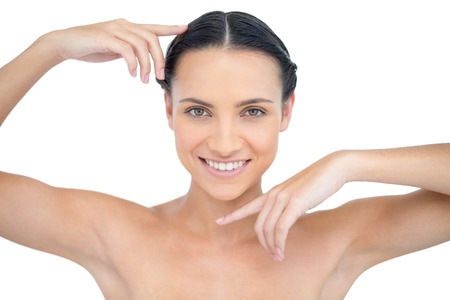 Smiling attractive topless model gesturing on white background photo