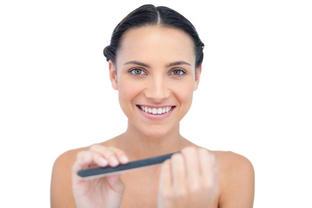 Smiling natural young model using nail file on white background Stock Photo - 25743144