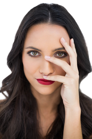 dark haired woman: Dark haired woman with red lips hiding her face on white background