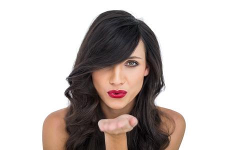 red lips: Morena atractiva con los labios rojos que sopla un beso a la cámara sobre fondo blanco Foto de archivo