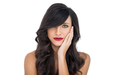 Sensual brunette with red lips touching her cheek on white background photo