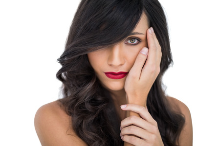 Glamorous brunette with red lips posing caressing her face on white background photo