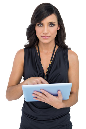 scrolling: Serious elegant brown haired model scrolling on tablet pc on white background