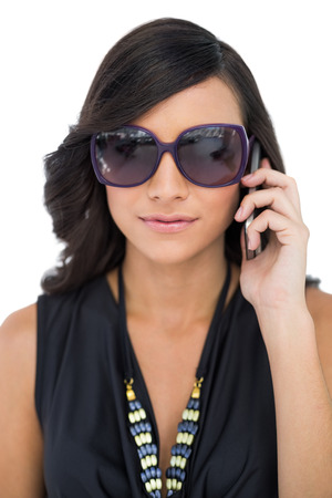 Elegant brunette wearing sunglasses on the phone on white background photo