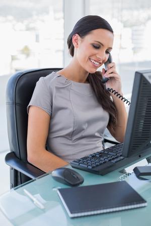 answering phone: Empresaria atractiva contestar el tel�fono en su oficina
