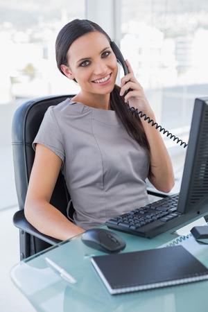 answering phone: Sonriendo atractivo tel�fono contestador de negocios en su oficina