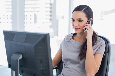 Peaceful dark haired businesswoman having a phone conversation in  her office photo