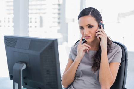 Thoughtful attractive businesswoman having a phone conversation in her office photo