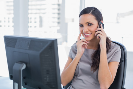 Happy attractive businesswoman having a phone conversation in her office photo