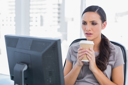 classy woman: Unsmiling attractive businesswoman in her office holding coffee