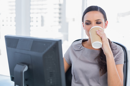 Attractive businesswoman drinking coffee and working in her office photo